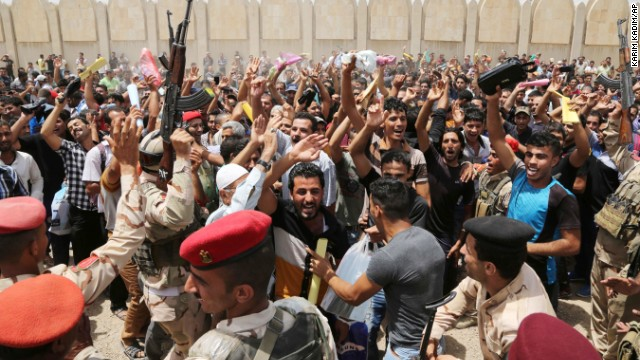 Iraqi men chant slogans against the al-Qaida breakaway group Islamic State of Iraq and the Levant (ISIL), outside of the main army recruiting center to volunteer for military service in Baghdad, Iraq, Thursday, June. 12, 2014, after authorities urged Iraqis to help battle insurgents.  The al-Qaida-inspired group that led the charge in capturing two key Sunni-dominated cities in Iraq this week vowed on Thursday to march on to Baghdad, raising fears about the Shiite-led government's ability to slow the assault following the insurgents' lightning gains. (AP Photo/ Karim Kadim)