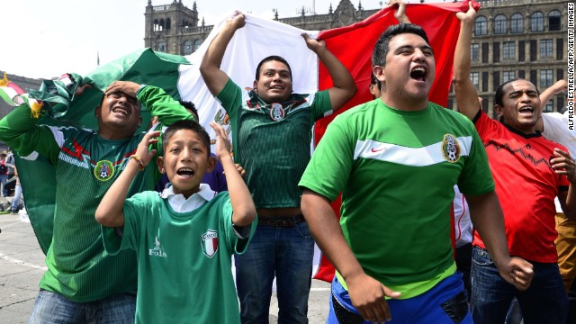 Mexican fans react at the Zocalo Square in Mexico City on June 13, 2014, as they watch the FIFA World Cup football match against Camerron on a screen. Mexico won by 1-0.