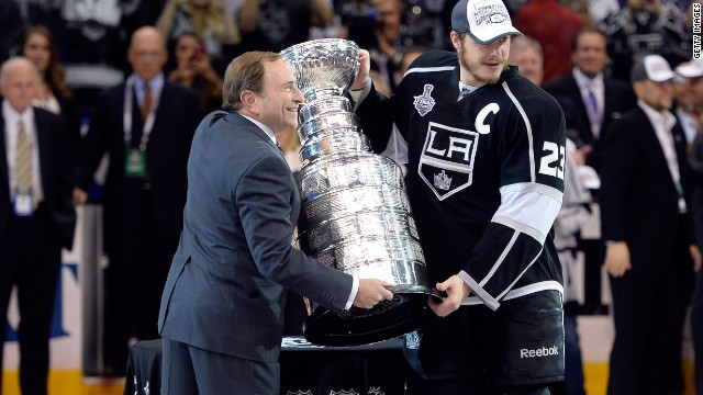 Dustin Brown of the L.A. Kings poses with NHL Commissioner Gary Bettman after the Kings won the Stanley Cup.
