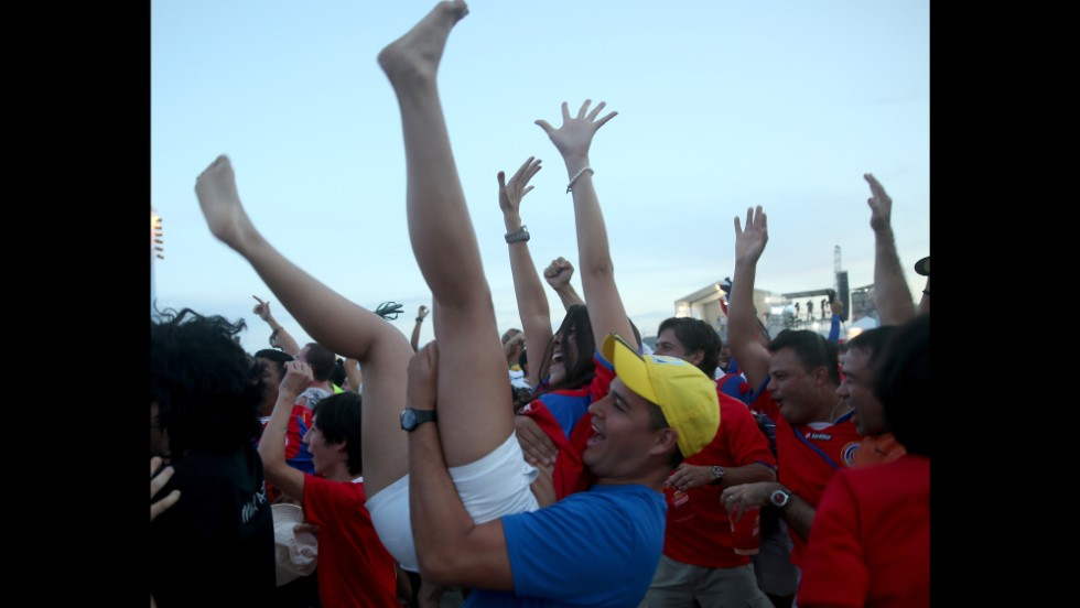 Costa Rica fans celebrate their team's first goal in the 3-1 win against Uruguay, watching the game on a giant screen on Copacabana beach in Rio de Janeiro, Brazil.