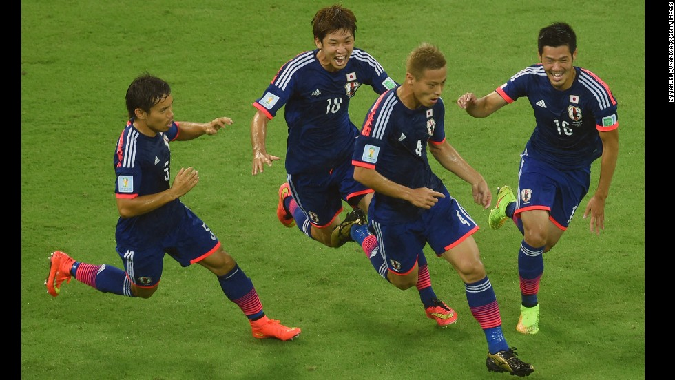 Keisuke Honda of Japan, second from right, celebrates scoring his team's first goal with Yuto Nagatomo, left, Yuya Osako, second from left, and Hotaru Yamaguchi, right