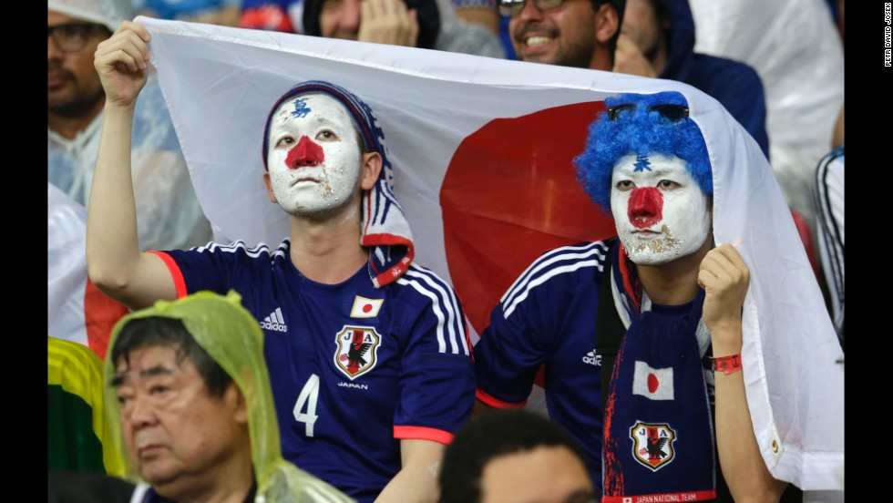 Japan fans protect themselves from the Brazilian rain with a Japanese flag.