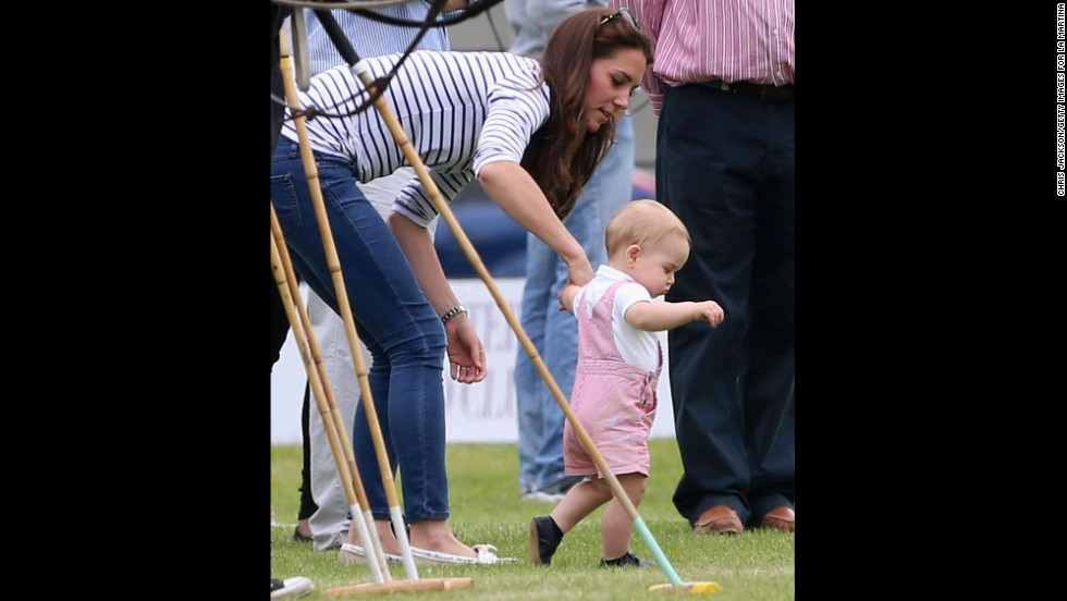 Prince George takes his first steps in public as his mother, Catherine, Duchess of Cambridge, holds his hand Sunday, June 15, at a charity polo event in Cirencester, England.