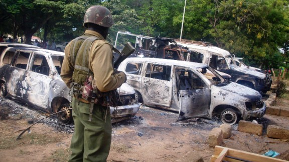 A member of the Kenyan security forces observes the remains of vehicles destroyed by militants, in the village of Kibaoni just outside the town of Mpeketoni, about 100 kilometers (60 miles) from the Somali border on the coast of Kenya Monday, June 16, 2014.