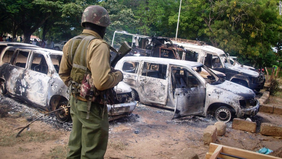A Kenyan security forces member stands guard near burnt-out vehicles in the village of Kibaoni, just outside Mpeketoni, on June 16.