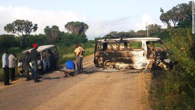 Men look at the wreckage of two vehicles sitting on the roadside in Mpeketoni.