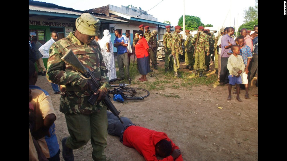 People stand near the body of a victim in Mpeketoni on June 16.