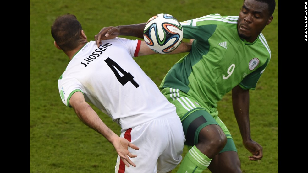 Iran's Jalal Hosseini fights for the ball with Emenike.