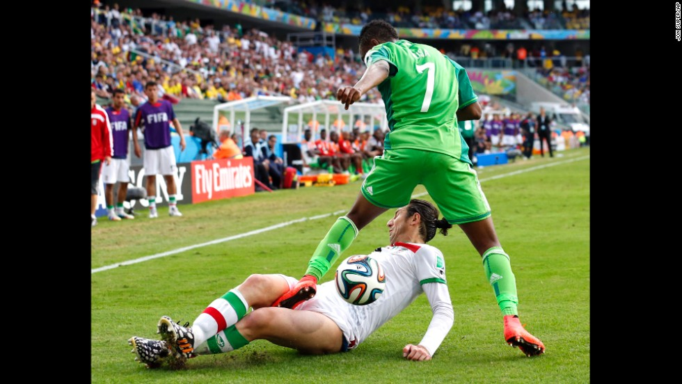 Iran's Andranik Teymourian slides under Nigeria's Ahmed Musa to take the ball away.