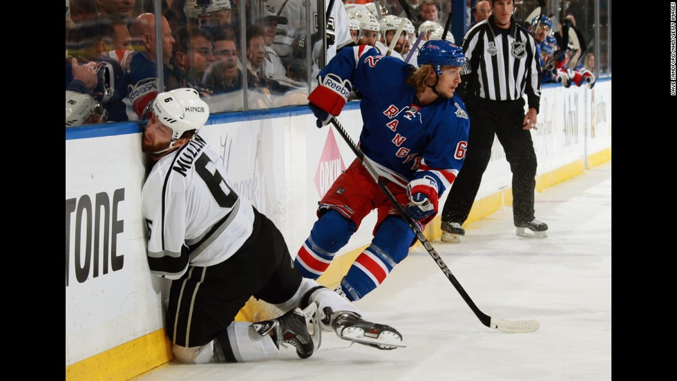Jake Muzzin of the Los Angeles Kings hits the wall in front of Carl Hagelin of the New York Rangers during Game 4 of the NHL Stanley Cup Final on Wednesday, June 11.