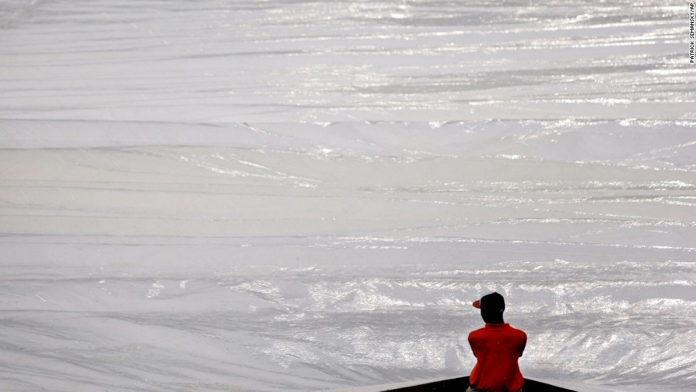 A Baltimore Orioles groundskeeper pulls a tarp over the infield during a rain delay Tuesday, June 10.