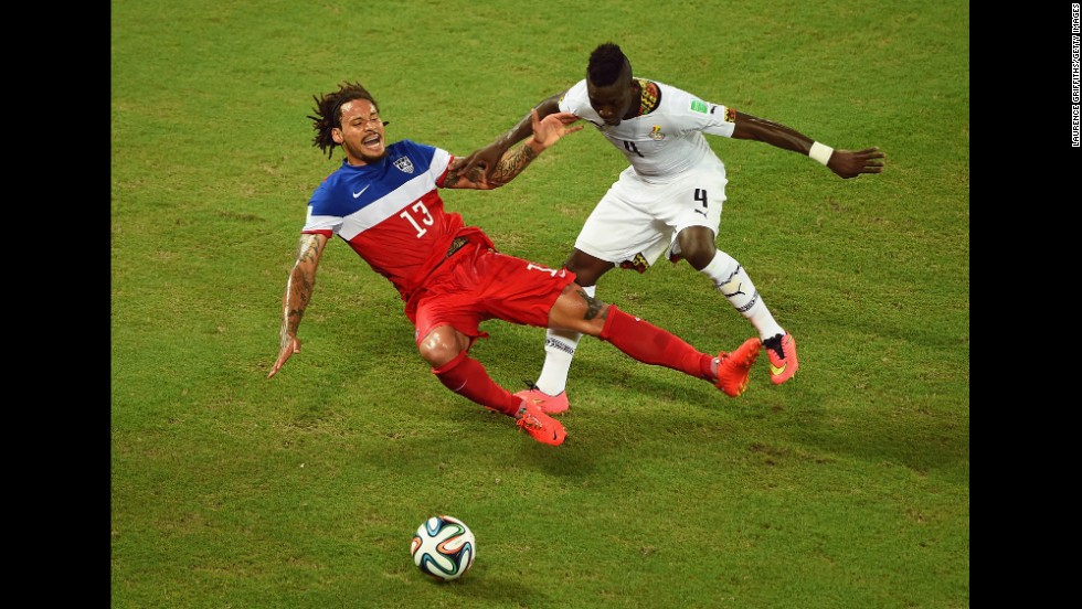 Jermaine Jones of the United States falls after a challenge from Ghana's Daniel Opare.