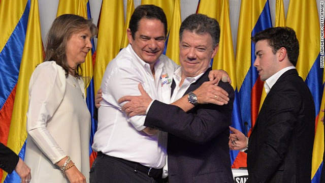 Colombian President and presidential candidate Juan Manuel Santos (C-R) celebrates with his Vice-President German Vargas Lleras (C-L) after knowing the results of the runoff presidential election on June 15, 2014, in Bogota. Santos was re-elected with 50.90 percent of the vote, compared with 45.04 percent for the more conservative Oscar Ivan Zuluaga, with 99.37 percent of votes tallied.