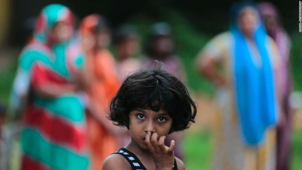 A  girl looks at a burned house in Aluthgama.
