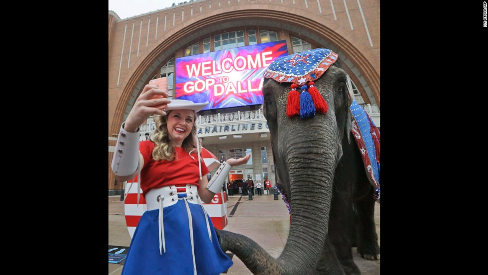 A Kilgore College Rangerette takes a selfie with an elephant in front of the American Airlines Center in Dallas, which was hosting members of the Republican National Committee on Thursday, June 12. The committee is scouting possible sites for the 2016 Republican National Convention.