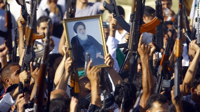 Iraqi Shiite tribesmen brandish their weapons and a poster of Shiite cleric Grand Ayatollah Ali al-Sistani in June 2014, as they gather to show their willingness to join Iraqi security forces in the fight against militants whod taken over several northern Iraqi cities.