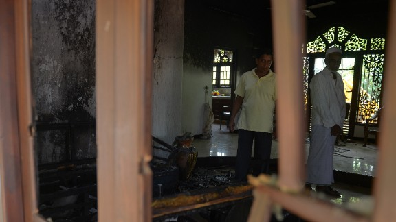 Sri Lankan residents survey the damage to a damaged Muslim-owned home.
