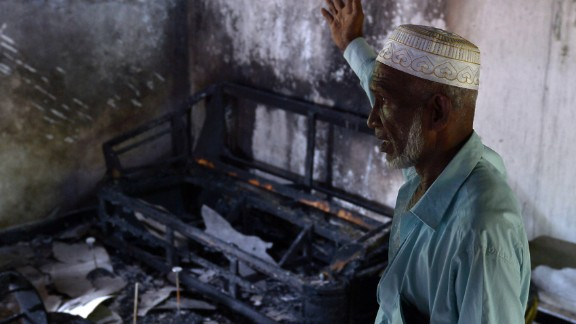 A Sri Lankan resident surveys the damage to a charred Muslim-owned home.