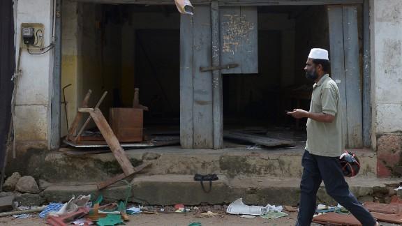 A Sri Lankan Muslim man walks past ransacked shops in Aluthgama.