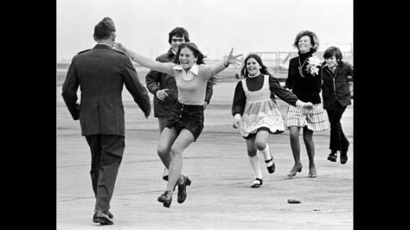 "Newly freed U.S. prisoner of war  Air Force Lt. Col. Robert L. Stirm is greeted by his family at Travis Air Force Base in Fairfield, California, in 1973. This Pulitzer Prize-winning photograph, named Burst of Joy, was taken by Associated Press photographer Sal Veder. ""You could feel the energy and the raw emotion in the air,"" Veder told Smithsonian Magazine in 2005."