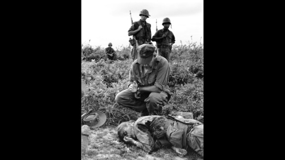 In this 1965 Henri Huet photograph, Chaplain John McNamara administers last rites to photographer Dickey Chapelle in South Vietnam. Chapelle was covering a U.S. Marine unit near Chu Lai for the National Observer when a mine seriously wounded her and four Marines. Chappelle died en route to a hospital, the first American woman correspondent ever killed in action.