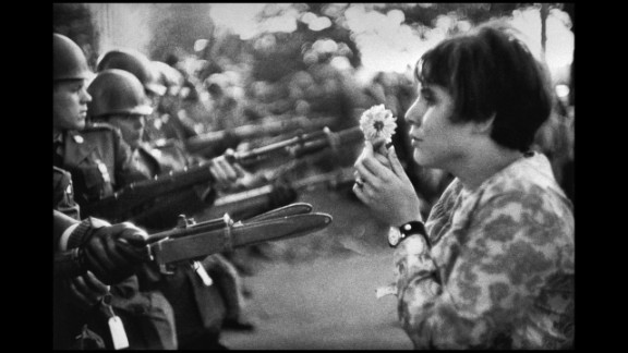"Frenchman Marc Riboud captured one of the most well-known anti-war images in 1967. Jan Rose Kasmir confronts National Guard troops outside the Pentagon during a protest march. The photo helped turn public opinion against the war. ""She was just talking, trying to catch the eye of the soldiers, maybe try to have a dialogue with them,"" recalled Riboud in the April 2004 Smithsonian magazine, ""I had the feeling the soldiers were more afraid of her than she was of the bayonets."""