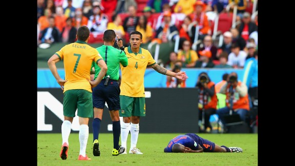 Referee Djamel Haimoudi speaks to Cahill after a challenge on Bruno Martins Indi of the Netherlands. Cahill received a yellow card for clattering into Martins Indi, and Martins Indi had to be taken off on a stretcher.