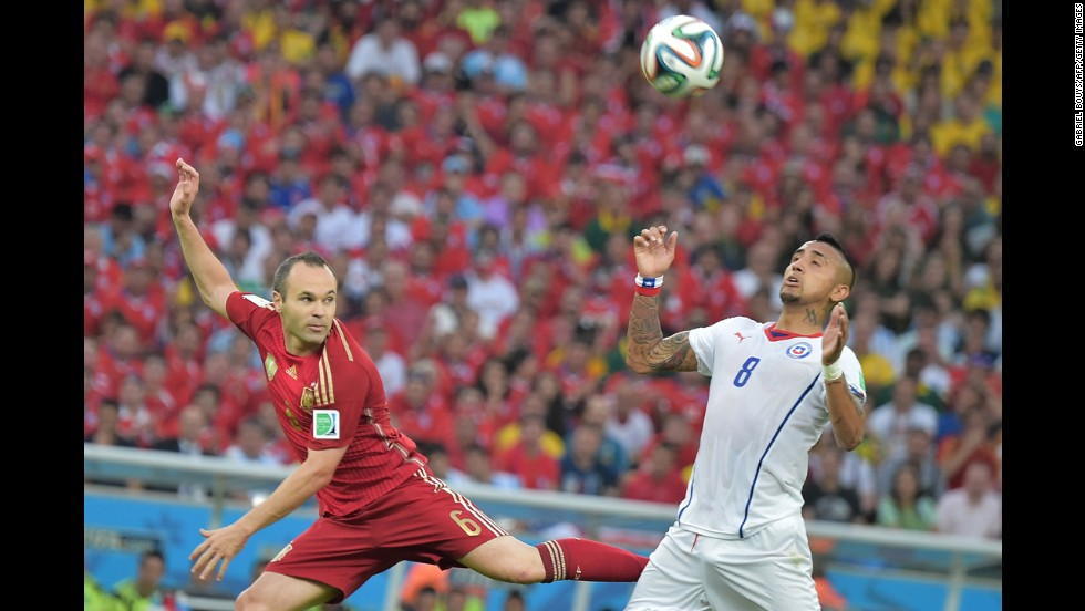 Iniesta and Chilean midfielder Arturo Vidal compete during the match.