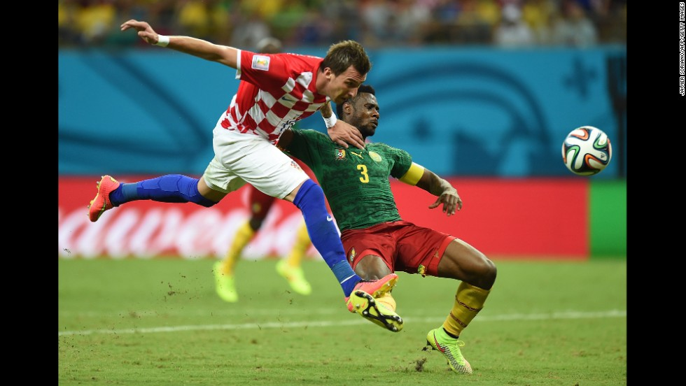 Croatia's Mario Mandzukic heads the ball past Cameroon's Nicolas Nkoulou.