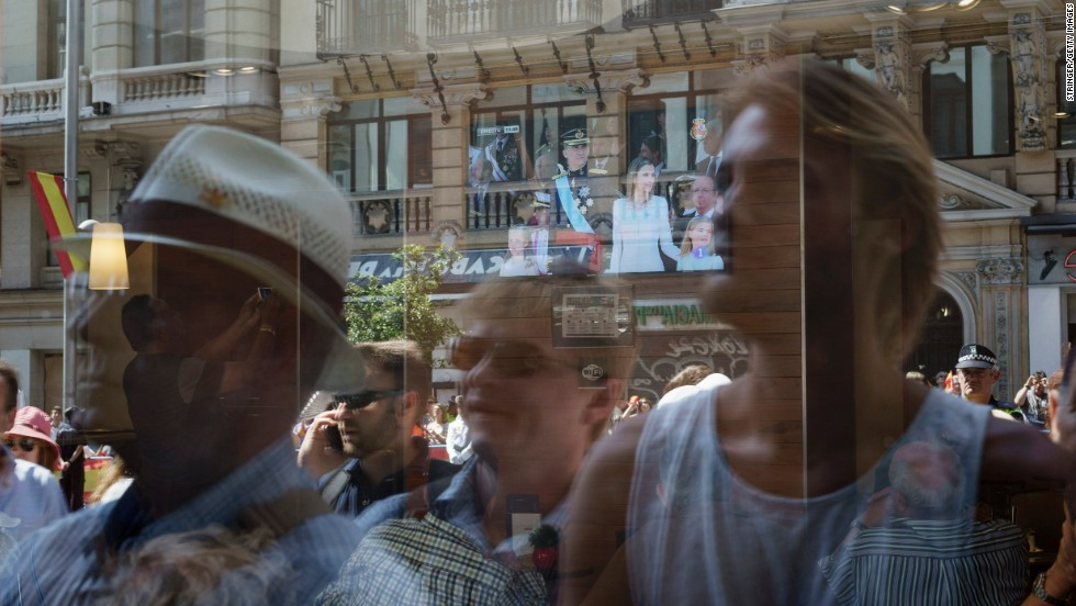 Well-wishers are reflected on a window as they gather at the royal palace.