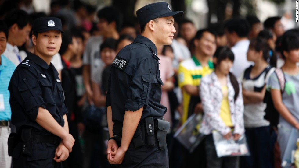 SWAT police stand guard as relatives wait outside a schoolyard as students sit the 2013 university entrance exam in Huaibei.