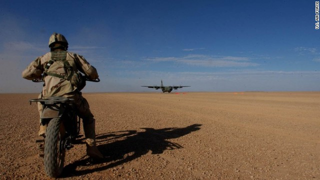 After preparing it for landing and providing air traffic control, an Air Force combat controller brings in a C-130 aircraft on a dirt strip in Afghanistan.