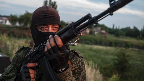 A pro-Russian fighter holds a gun during a handover of the bodies of Ukrainian troops killed in a plane shot down near Luhansk, at a check point in the village of Karlivka near Donetsk, eastern Ukraine, Wednesday, June 18, 2014.