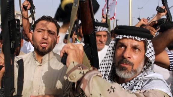 Iraqi Shiite men brandish their weapons as they show their willingness to join Iraqi security forces in the fight against Jihadist militants who have taken over several northern Iraqi cities, on June 18, 2014, in the capital Baghdad.