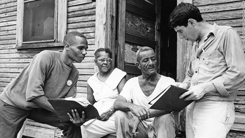Johnny Waters, Ceola Wallace and Jake Plum explain registration procedures to prospective voter Willie McGee in Hattiesburg, Mississippi.