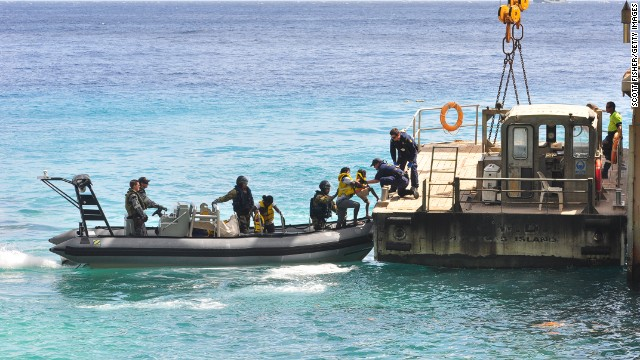 Suspected asylum seekers arrive on Christmas Island, after being intercepted by the Australian Navy, on August 3, 2013.