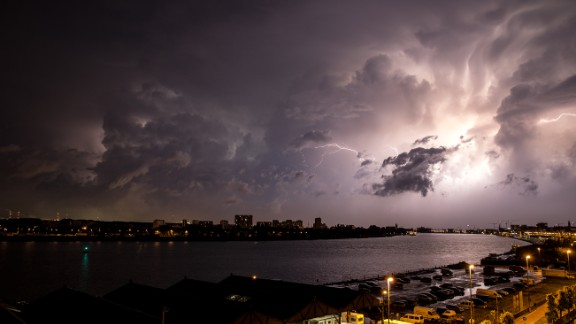 "In Antwerp, Belgium, Zachary Koulermos was woken up by a hailstorm in June. After the hail subsided, the rain brought an ""amazing lightning storm,"" he said. He grabbed his camera and tripod as the clouds retreated."