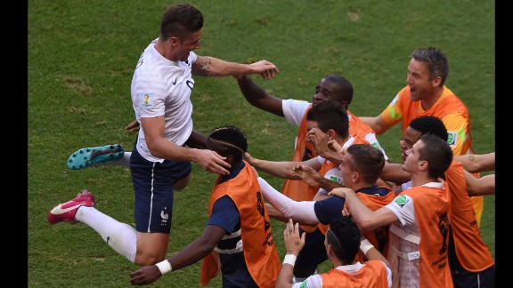 After scoring the opening goal of the match, Giroud celebrates with his French teammates on the sideline.