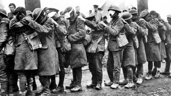 "Men of the British Army's 55th Division, blinded by a poison gas attack, in April 1918. British soldier Wilfred Owen captured the panic of an attack in verse ""Gas! Gas! Quick, boys! -- An ecstasy of fumbling, Fitting the clumsy helmets just in time; But someone still was yelling out and stumbling, And flound'ring like a man on fire or lime."""