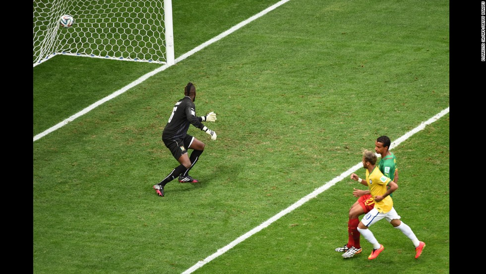 Brazil forward Neymar, right, scores Brazil's first goal past Cameroon goalkeeper Charles Itandje.
