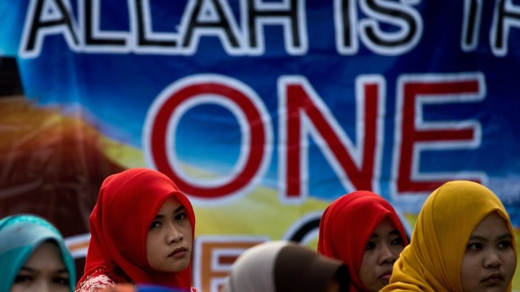 Muslim activists wait outside Malaysia's highest court in Putrajaya for the verdict on June 23, 2014.