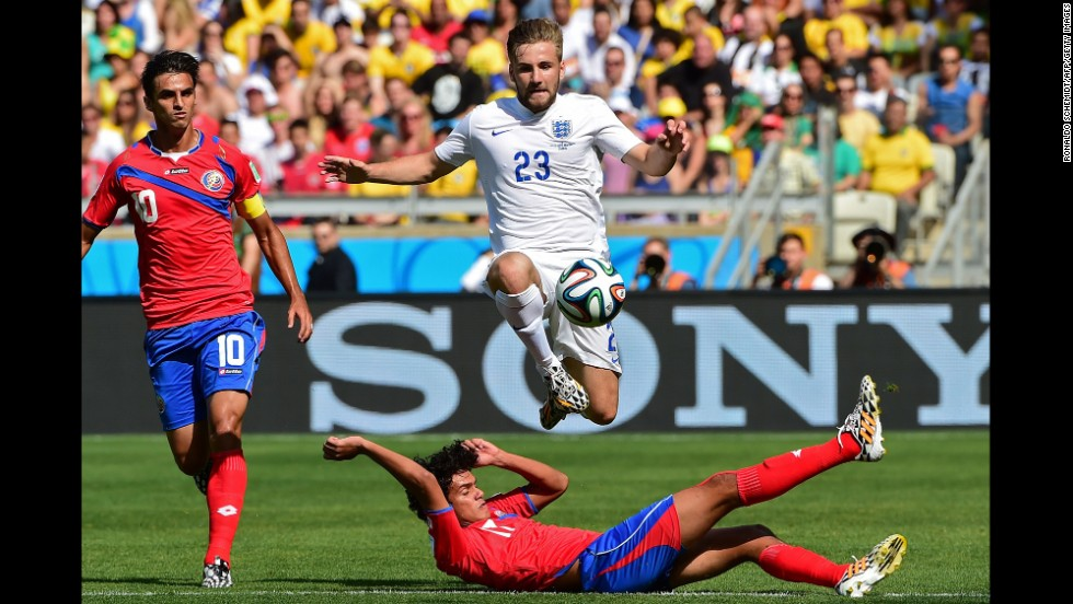 England defender Luke Shaw jumps over a Costa Rica player while going after the ball.