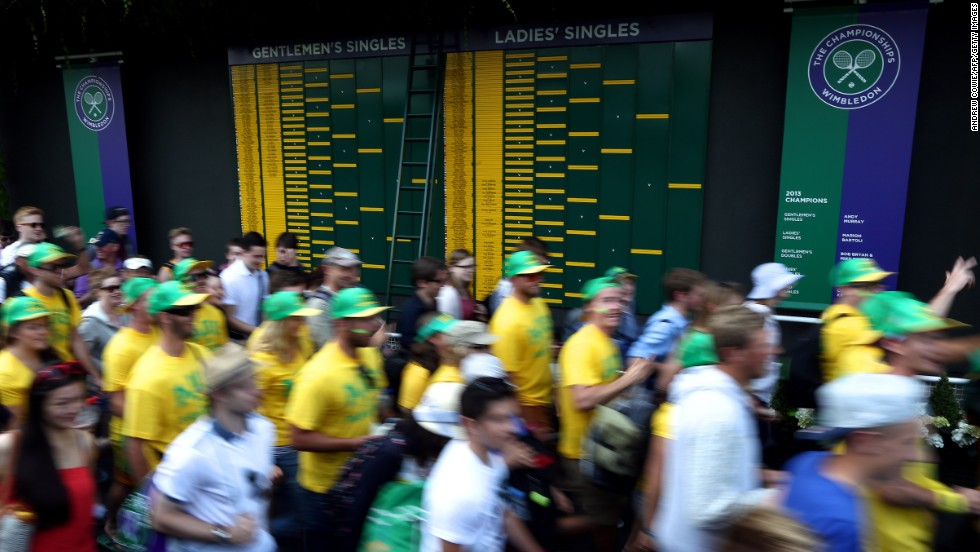 Spectators walk past the order-of-play boards at the All England Tennis Club.