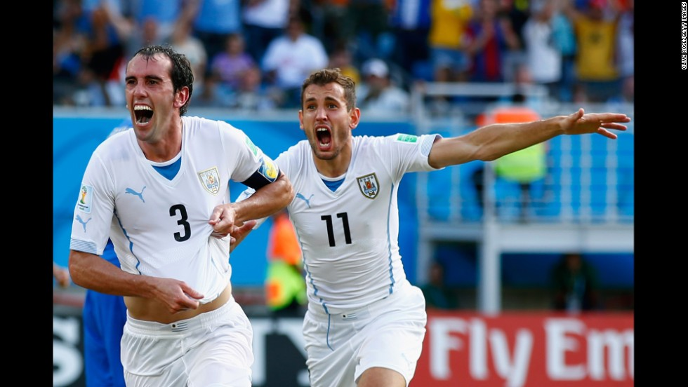 Diego Godin of Uruguay, left, celebrates scoring his team's first goal during a match against Italy in Natal, Brazil. Uruguay won 1-0.