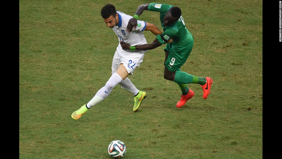 Greece's Andreas Samaris, left, fights for the ball with Ivory Coast's Ismael Cheick Tiote.