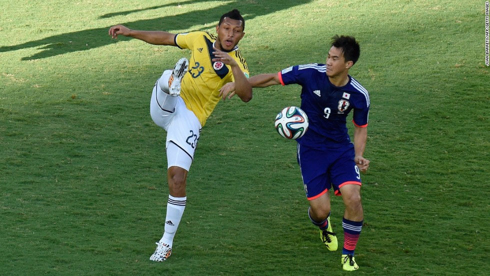 Colombia's Carlos Valdes, left, vies for the ball with Japan's Shinji Okazaki during a World Cup match in Cuiaba, Brazil.