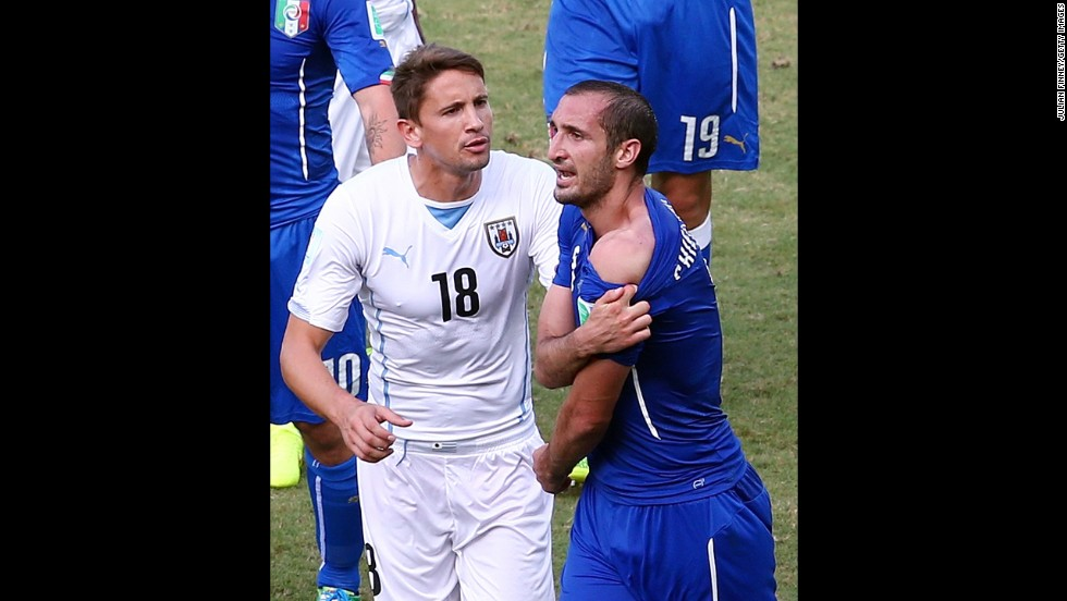 Television pictures showed Suarez dipping his head towards Chiellini, right, and when the Italian defender eventually got up, he pulled down his shirt and appeared to furiously indicate that he had been bitten on the shoulder.
