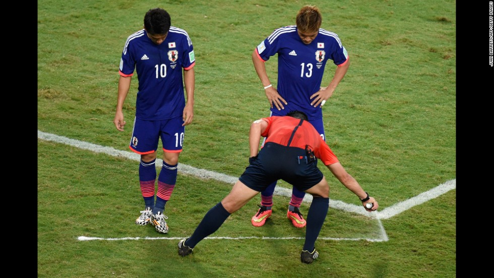 Referee Pedro Proenca sprays a free kick line during the match between Japan and Colombia.