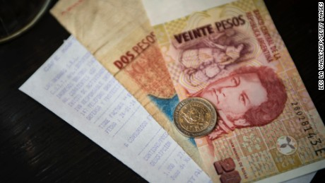 A ticket and Argentine money are seen in a cofee bar in Buenos Aires downtown on January 24, 2014. Argentine pesos bills in Buenos Aires on January 24, 2014. Argentina on Friday lifted restrictions in place since 2011 that limited the purchase of foreign currency, a day after the peso suffered its worst single-day dive since the 2002 financial crisis. The government has decided 'to authorize the purchase of dollars for holding or savings,' said Jorge Capitanich, President Cristina Kirchner's cabinet chief. The restrictions had always been temporary and had served their purpose. AFP PHOTO / LEO LA VALLE (Photo credit should read LEO LA VALLE/AFP/Getty Images)