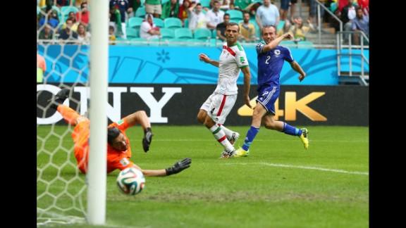 Avdija Vrsajevic of Bosnia-Herzegovina shoots and scores his team's third goal past goalkeeper Alireza Haghighi of Iran during a match in Salvador, Brazil, on June 25. Bosnia-Herzegovina won 3-1.